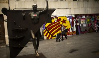 """A woman pushes a trolley past a graffiti of an """"estelada"""", or Catalonia independence flag, at the Gracia neighborhood in Barcelona, Wednesday, Oct. 4, 2017. Catalonia's regional government is mulling when to declare the region's independence from Spain in the wake of a disputed referendum that has triggered Spain's most serious national crisis in decades. (AP Photo/Francisco Seco)"""
