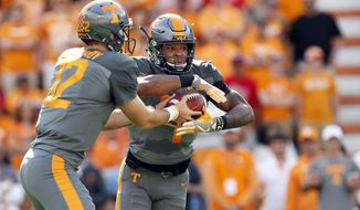 "FILE - In this Sept. 30, 2017 file photo, Tennessee running back John Kelly takes a handoff from quarterback Quinten Dormady (12) during a 41-0 loss to Georgia in an NCAA college football game in Knoxville, Tenn. Kelly called Tennessee's off week a ""reality check"" in the wake of the loss to Georgia, the Vols' most lopsided home defeat since 1905. The Georgia game also marked the first time Tennessee had been shut out since 1994. (AP Photo/Wade Payne, File)"