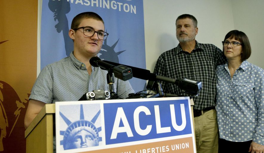 Paxton Enstad, left, addresses a news conference about a lawsuit filed over refusal by an insurance plan to cover his gender-reassignment surgery as his parents, Cheryl and Mark Enstad, look on Thursday, Oct. 5, 2017, in Seattle. The American Civil Liberties Union of Washington filed the discrimination lawsuit against PeaceHealth in federal court on behalf of Cheryl Enstad, of Bellingham, and her son. The lawsuit cites violations of the federal Affordable Care Act as well as Washington state anti-discrimination law. (AP Photo/Elaine Thompson)