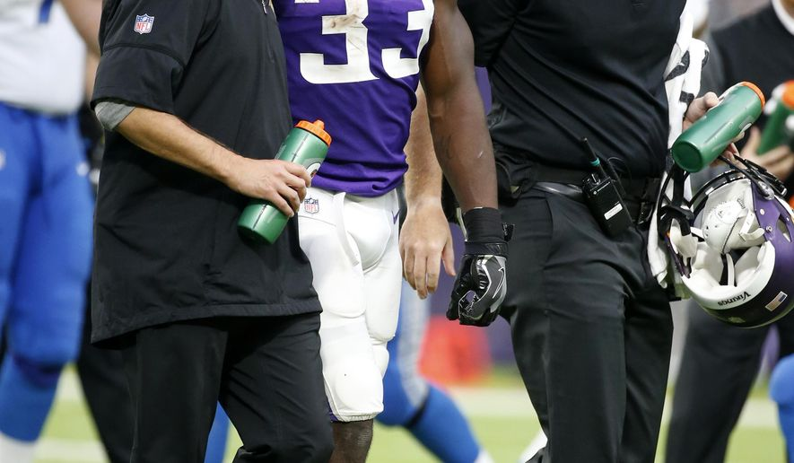 FILE - In this Sunday, Oct. 1, 2017, file photo, Minnesota Vikings running back Dalvin Cook, center, grimaces as he is helped off the field after getting injured in the second half of an NFL football game against the Detroit Lions in Minneapolis. Cook became the latest integral offensive player lost by the bad-luck-trodden Vikings. The team's fear of a torn ACL in the rookie running back's left knee was realized Monday, sealing the end of a promising rookie season. (AP Photo/Bruce Kluckhohn, File)