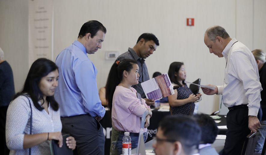 In this Thursday, Aug. 24, 2017, file photo, Phil Wiggett, right, a recruiter with the Silicon Valley Community Foundation, looks at a resume during a job fair in San Jose, Calif. On Friday, Oct. 6, 2017, the U.S. government issues the September jobs report. (AP Photo/Marcio Jose Sanchez)