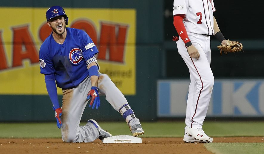 Chicago Cubs' Kris Bryant reacts after reaching second base on an RBI double scoring teammate Javier Baez in the sixth inning against the Washington National in Game 1 of baseball's National League Division Series, at Nationals Park, Friday, Oct. 6, 2017, in Washington. Also on the field is Nationals' Trea Turner. (AP Photo/Pablo Martinez Monsivais)