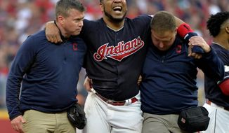 Cleveland Indians' Edwin Encarnacion is carried off the field after rolling his ankle at second base in the second inning of Game 2 of baseball's American League Division Series against the New York Yankees, Friday, Oct. 6, 2017, in Cleveland. (AP Photo/Phil Long)