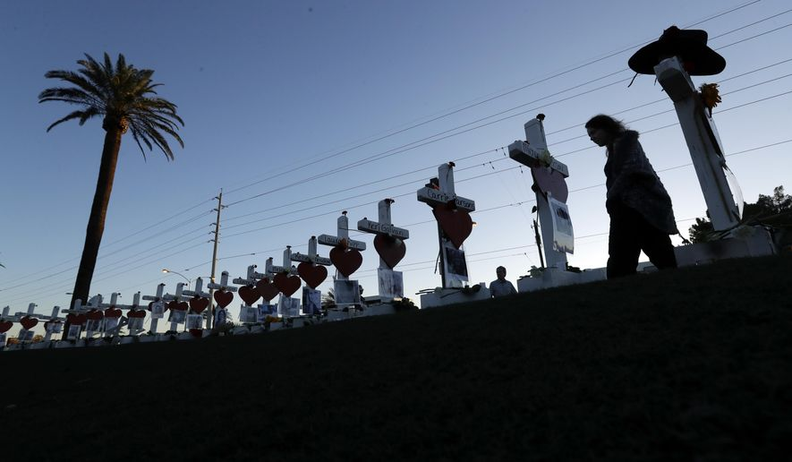 Manuela Barela passes crosses set up to honor those killed during the mass shooting Friday, Oct. 6, 2017, in Las Vegas. A gunman, Stephen Paddock, opened fire on an outdoor music concert on Sunday killing dozens and injuring hundreds.(AP Photo/Gregory Bull)