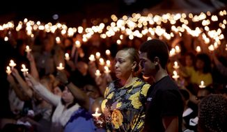 Veronica Hartfield, stands with her son, Ayzayah Hartfield during a candlelight vigil for her husband, Las Vegas police officer Charleston Hartfield, Thursday, Oct. 5, 2017, in Las Vegas. Hartfield was killed during the Sunday night shooting at the Route 91 Harvest country music festival. (AP Photo/Gregory Bull)