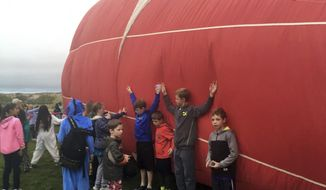 Students at Enchanted Hills Elementary School in Rio Rancho, N.M. lean against a balloon from the upcoming Albuquerque International Balloon Fiesta on Friday, Oct. 6, 2017. The 46th Albuquerque International Balloon Fiesta is set to begin Saturday and is expected to draw close to a million visitors to central New Mexico. (AP Photo/Russell Contreras)