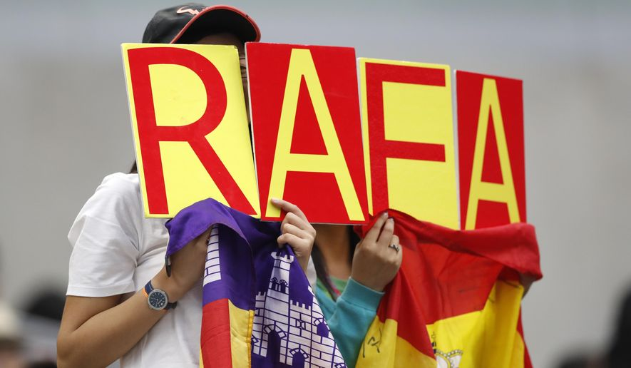 Chinese fans hold the Spanish national flag and cards to cheer on Rafael Nadal of Spain as he plays against against Karen Khachanov of Russia in their second round of the men's singles match in the China Open tennis tournament at the Diamond Court in Beijing, Thursday, Oct. 5, 2017. (AP Photo/Andy Wong)