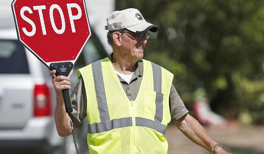 In this Sept. 9, 2017 file photo, George Caspermeyer smiles while directing traffic as a  crossing guard for Madison School students in Quincy, Ill. Caspermeyer has worked the corner for the last 19 years and plans to not work when the school closes. The retired-Moorman Manufacturing fork lift driver and longtime guard that has guided kids to safety across the street as they walk home will step down when Madison closes next year. With the transitioning of students into a new buildings, there will be less demand for crossing guards. (Jake Shane /The Quincy Herald-Whig via AP)