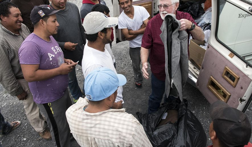 In a Monday, Aug. 28, 2017 photo, migrant workers laugh as Reverend Roddy Runyan unloads a bag of sport coats, mistaking the coats for a bag of sweatshirts, in Carlisle, Pa Fruitbelt Farmworker Christian Ministry provides items to migrant workers, from sweatshirts to toiletries to bibles. Reverend Roddy Runyan has been making rounds to help migrant workers since 1990.  (Ty Lohr/The Evening Sun via AP)