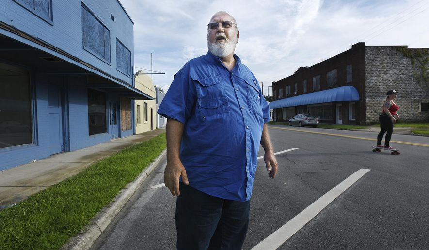 Hastings mayor Tom Ward stands along the quiet main street of his town where most of the buildings are vacant despite sporadic attempts by businesses over the years to try and stay in business, on Friday, Aug. 11, 2017 in Hastings, Fla.  Hastings, with a population of around 600 people, is considering a vote to dissolve it as a town and turn what is left of the town's functions over to St. Johns County.  (Bob Self/The Florida Times-Union via AP)