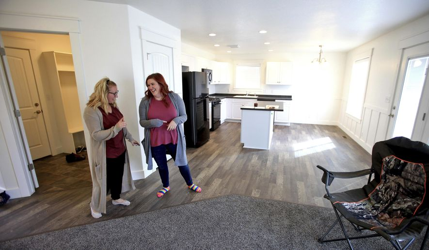 In this Sept. 2017, photo, Loryn Law, right, laughs with Mikell Brown during a tour of her new Hyrum, Utah, home that was recently completed through the Neighborhood Housing Solutions program. (John Zsiray/The Herald Journal via AP)