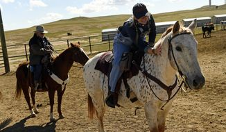 In this Sept. 26, 2017 photo, Rachel Hunsell, an executive coordinator for TAPS, pets her horse Jessup during a retreat at the Colorado Cattle Company, in New Raymer, Colo. The Tragedy Assistance Program for Survivors (TAPS) hosted families of America's fallen military heroes for a week long retreat at the cattle ranch. The six-day event was filled with challenging new activities for participants and offered attendees the opportunity to honor their loved one, connect with peers during shared experiences and provide them with tools to cope with their grief. Since 1994, the program has assisted 70,000 surviving family members, casualty officers and caregivers of those who have lost loved ones. The organization provides a variety of programs to survivors nation and worldwide. (Helen H. Richardson/The Denver Post via AP)