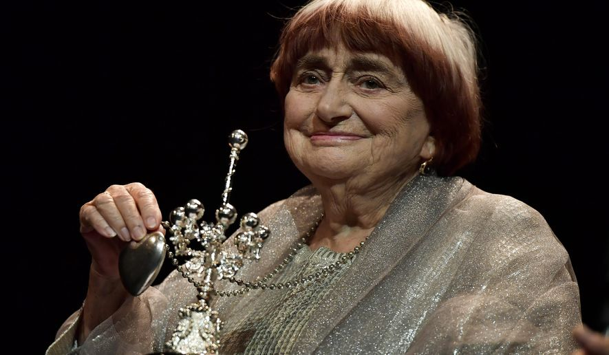 FILE - In this Sept. 24, 2017 file photo, film director Agnes Varda holds the Donostia Award for her contribution to the cinema at the 65th San Sebastian Film Festival, in San Sebastian, northern Spain. Varda reflects on her life in cinema, her status as a trailblazer for female filmmakers and the lifetime achievement award she'll receive from the Academy Awards. (AP Photo/Alvaro Barrientos, File)
