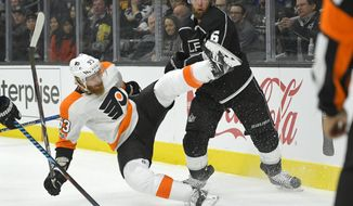Philadelphia Flyers right wing Jakub Voracek, of the Czech Republic, falls as he battles for the puck with Los Angeles Kings defenseman Jake Muzzin during the first period of an NHL hockey game, Thursday, Oct. 5, 2017, in Los Angeles. (AP Photo/Mark J. Terrill)
