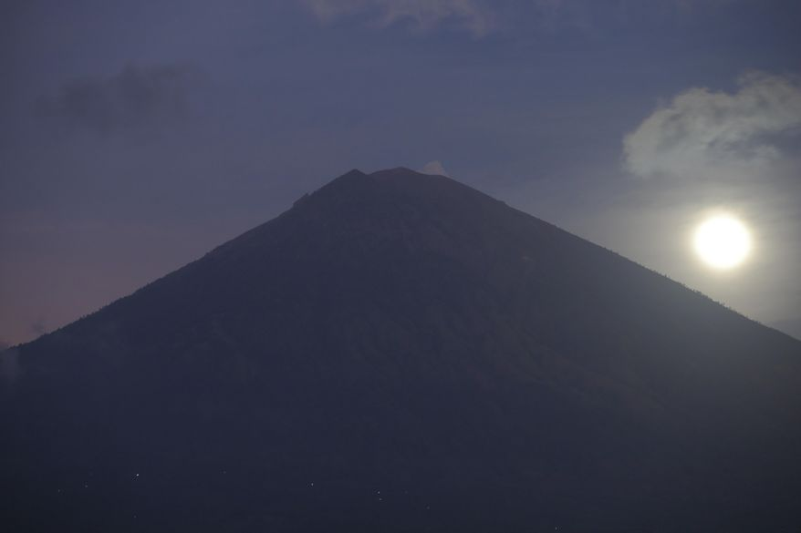 A full moon is set behind the Mount Agung volcano in Karangasem, Bali, Indonesia, Friday, Oct. 6, 2017. More than 140,000 people have fled from the surrounds of Mount Agung since authorities raised the volcano's alert status to the highest level on Sept. 22 after a sudden increase in tremors. It last erupted in 1963, killing more than 1,000 people. (AP Photo/Firdia Lisnawati)