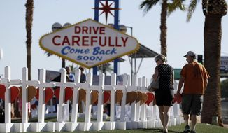 People walk by crosses placed near Las Vegas' famous sign Thursday, Oct. 5, 2017, in Las Vegas. The crosses are in honor of those killed when Stephen Craig Paddock broke windows on the Mandalay Bay resort and casino and began firing with a cache of weapons at a country music festival Sunday. Dozens of people were killed and hundreds were injured. (AP Photo/Gregory Bull)