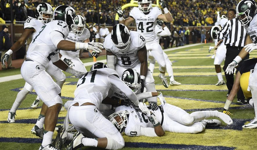FILE - In this Saturday, Oct. 17, 2015 file photo, Michigan State defensive back Jalen Watts-Jackson (20) is surrounded by jubilant teammates after he recovered a fumbled snap on a punt in the closing seconds of the second half and returned it for a touchdown during an NCAA college football game against Michigan in Ann Arbor, Mich. Michigan State's last visit to the Big House ended with Michigan botching a punt and blowing a chance to beat the Spartans in a series they've controlled for nearly a decade. Michigan plays Michigan State on Saturday, Oct. 7, 2017. (Melanie Maxwell/The Ann Arbor News/MLive.com via AP, File)
