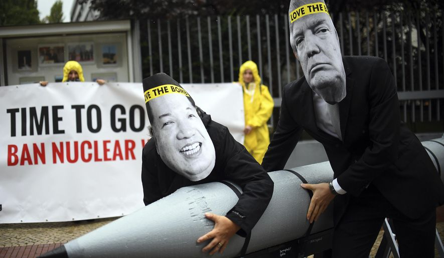 In this Sept. 13, 2017, file photo activists of the International Campaign to Abolish Nuclear Weapons (ICAN) protest against the conflict between North Korea and the USA with masks of the North Korean ruler, Kim Jong-un, left, and U.S. President Donald Trump, right, in front of the U.S. Embassy in Berlin, Germany. (Britta Pedersen/dpa via AP)