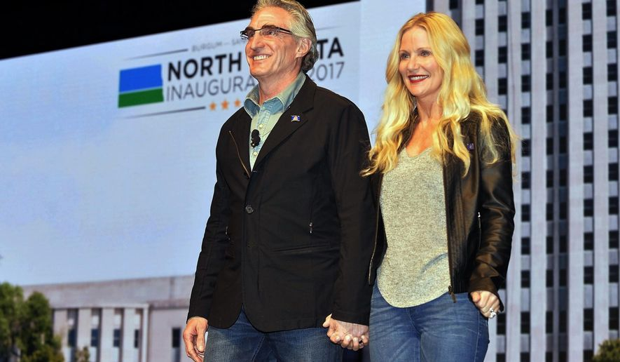 FILE - In this Jan. 4, 2017 photo, North Dakota Gov. Doug Burgum and first lady Kathryn Helgaas Burgum greet the crowd at the governor's inauguration celebration in Bismarck, N.D. The former tech executive Burgum's Silicon Valley-styled approach to leading North Dakota government has sparked conflicts with longtime Republican power brokers. He replaced his office desk chair with a wellness ball, frequently wears jeans and assigned subordinates corporate titles. But a looming conflict extends far beyond style. (Will Kincaid /The Bismarck Tribune via AP, File)