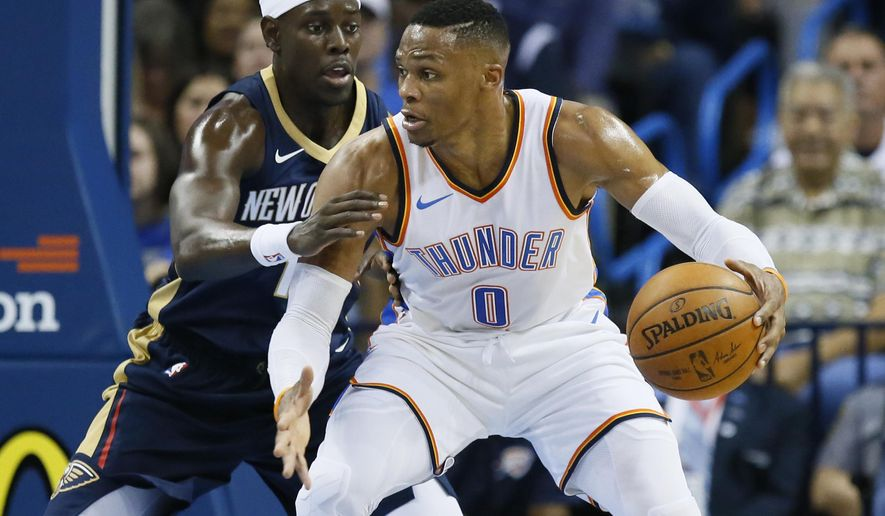 Oklahoma City Thunder guard Russell Westbrook (0) drives against New Orleans Pelicans guard Jrue Holiday, left, during the first quarter of an NBA preseason basketball game in Oklahoma City, Friday, Oct. 6, 2017. (AP Photo/Sue Ogrocki)