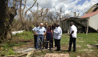 Vice President Mike Pence, joined by his wife Karen Pence, fourth from left, surveys hurricane damage outside Holy Cross Episcopal Church in St. Croix, U.S. Virgin Islands on Friday, Oct. 6, 2017. The church suffered  extensive damage, including large holes in the roof. (AP Photo/Kenneth Thomas)
