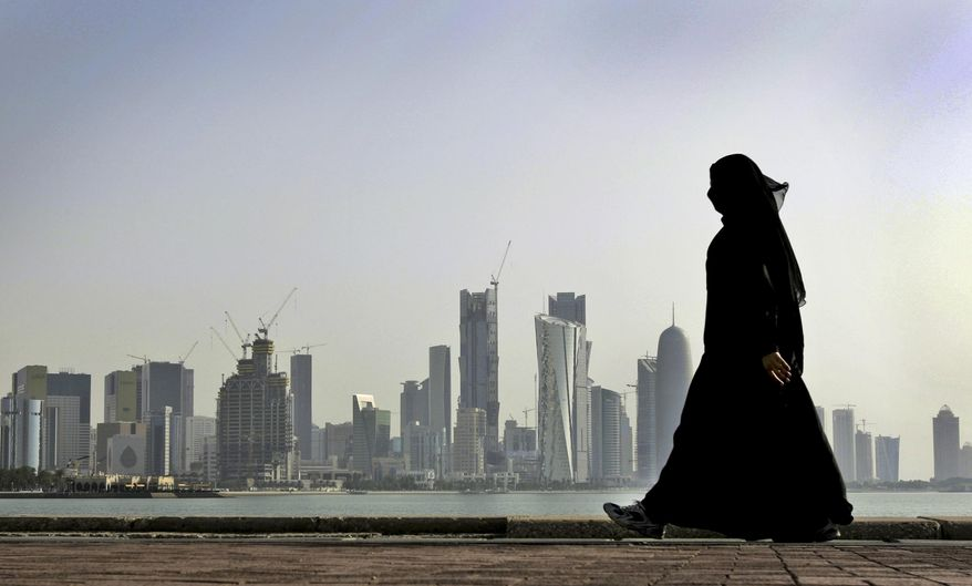 FILE- In this May 14, 2010 file photo, a Qatari woman walks in front of the city skyline in Doha, Qatar. The U.S. military says it has halted some military exercises with Gulf countries over the ongoing diplomatic dispute targeting Qatar. (AP Photo/Kamran Jebreili, File)