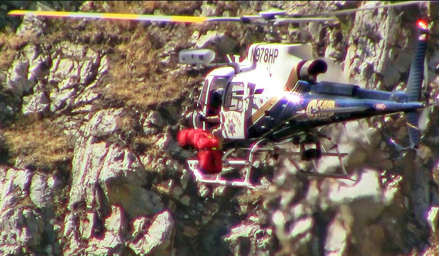 This Thursday, Oct. 5, 2017 frame from video provided by the Fresno County, Calif., Sheriff's Department shows a California Highway Patrol helicopter carrying one of two bodies recovered from a car that plunged off a cliff into the Kings River in Kings Canyon National Park weeks ago. The bodies are believed to be those of a Chinese couple who were in the car, but positive identification has not been made. (Fresno County Sheriff's Department via AP)