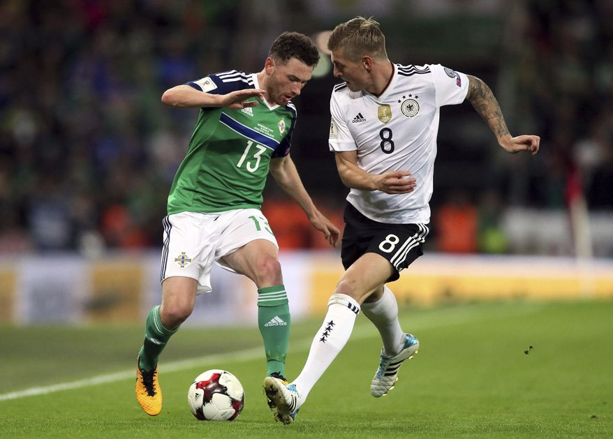 Northern Ireland's Corry Evans, left, and Germany's Toni Kroos battle for the ball during their 2018 World Cup Group C qualifying soccer match at Windsor Park, Belfast, Thursday, Oct. 5, 2017. (Brian Lawless/PA via AP)