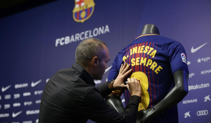 "FC Barcelona's Andres Iniesta signs a shirt reading in Catalan: ""Andres Iniesta forever"" at the Camp Nou stadium in Barcelona, Spain, Friday, Oct. 6, 2017. Barcelona has extended Andres Iniesta's contract ""for life."". (AP Photo/Manu Fernandez)"