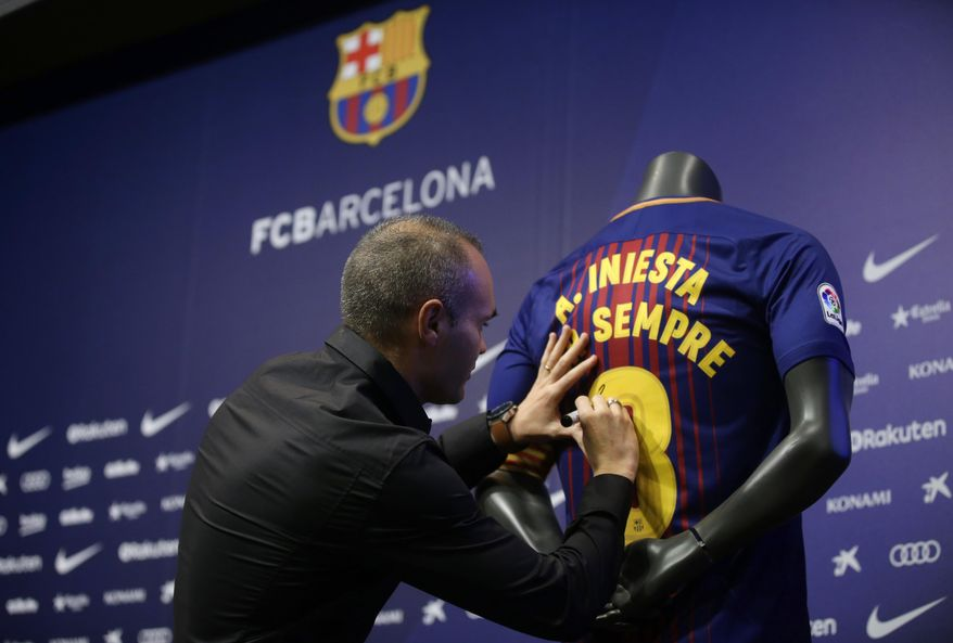 """FC Barcelona's Andres Iniesta signs a shirt reading in Catalan: """"Andres Iniesta forever"""" at the Camp Nou stadium in Barcelona, Spain, Friday, Oct. 6, 2017. Barcelona has extended Andres Iniesta's contract """"for life."""". (AP Photo/Manu Fernandez)"""