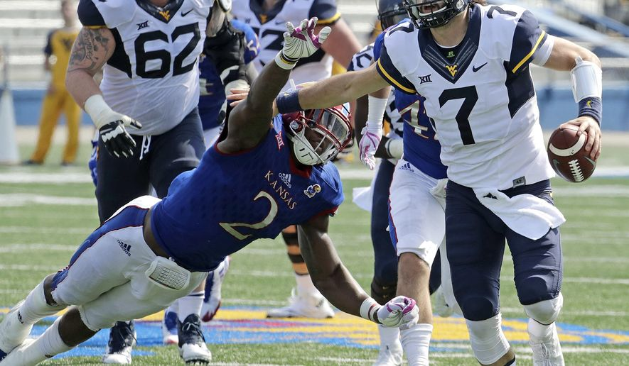 FILE - In this Sept. 23, 2017, file photo, West Virginia quarterback Will Grier (7) evades Kansas defensive end Dorance Armstrong Jr. (2) as he runs for a first down during the second half of an NCAA college football game in Lawrence, Kan. Grier and TCU's Kenny Hill took similar paths to the Big 12, and their head-to-head matchup is the only game Saturday matching two Top 25 teams.(AP Photo/Charlie Riedel, File)