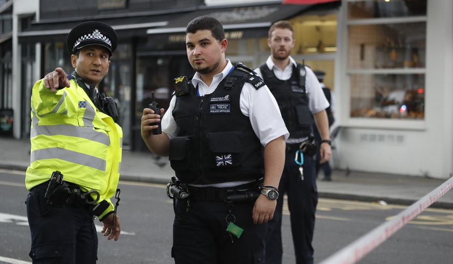 Britain's policemen at the scene of an incident in central London, Saturday, Oct. 7, 2017. London police say emergency services are outside the Natural History Museum in London after a car struck pedestrians. (AP Photo/Kirsty Wigglesworth)