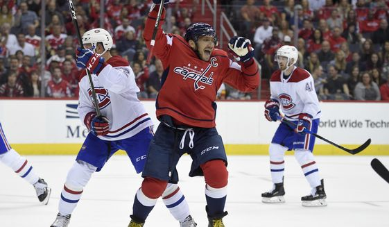 Washington Capitals left wing Alex Ovechkin (8), of Russia, celebrates his goal next to Montreal Canadiens defenseman Karl Alzner (22) during the first period of a NHL hockey game, Saturday, Oct. 7, 2017, in Washington. This was Ovechkin's third goal of the period and the game. (AP Photo/Nick Wass)