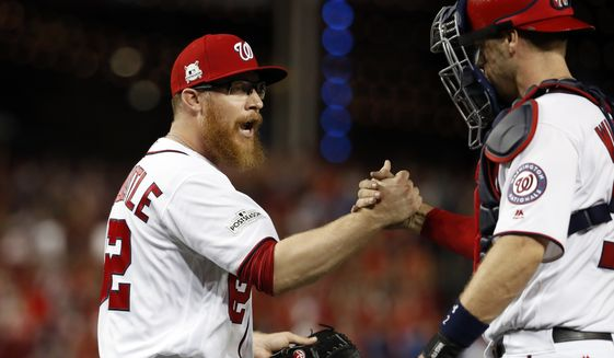 Washington Nationals relief pitcher Sean Doolittle, left, celebrates with catcher Matt Wieters after Game 2 of baseball's National League Division Series against the Chicago Cubs, at Nationals Park, Saturday, Oct. 7, 2017, in Washington. The Nationals won 6-3. (AP Photo/Alex Brandon)