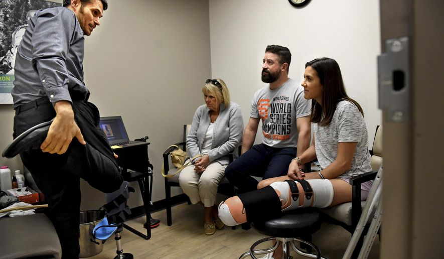 "In a Friday, Sept. 29, 2017 photo, prosthetist Yakov ""Jacob"" Gradinar, left, talks with Courtney Godfrey, right, her husband, Ryan Novaczyk, and her mother, Barbara Godfrey, before he does casting for a temporary bent-knee prosthesis at Hanger Clinic in Minneapolis. Godfrey lost her lower leg following a boating accident Sept. 15. (Jean Pieri/Pioneer Press via AP)"