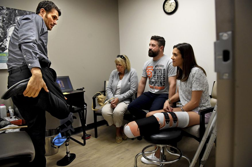 """In a Friday, Sept. 29, 2017 photo, prosthetist Yakov """"Jacob"""" Gradinar, left, talks with Courtney Godfrey, right, her husband, Ryan Novaczyk, and her mother, Barbara Godfrey, before he does casting for a temporary bent-knee prosthesis at Hanger Clinic in Minneapolis. Godfrey lost her lower leg following a boating accident Sept. 15. (Jean Pieri/Pioneer Press via AP)"""