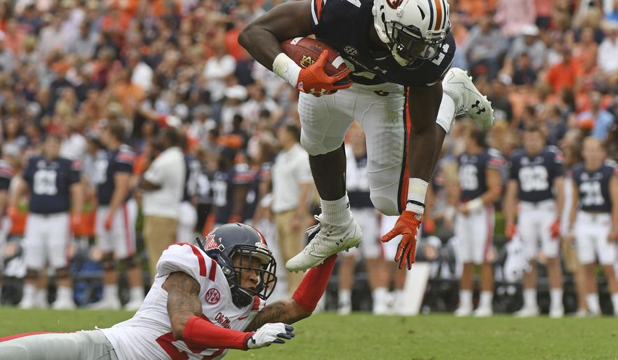 Mississippi defensive back Javien Hamilton (21) trips up Auburn running back Kerryon Johnson (21) during the first half of an NCAA college football game in Auburn, Ala., Saturday, Oct. 7, 2017. (AP Photo/Thomas Graning)