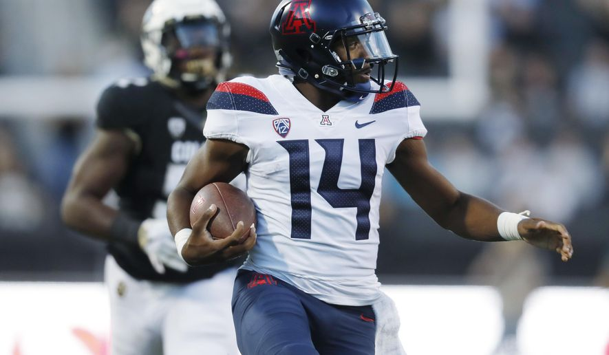 Arizona quarterback Khalil Tate, front, runs past Colorado defensive end Leo Jackson III on the way to a touchdown in the first half of an NCAA college football game Saturday, Oct. 7, 2017, in Boulder, Colo. (AP Photo/David Zalubowski)