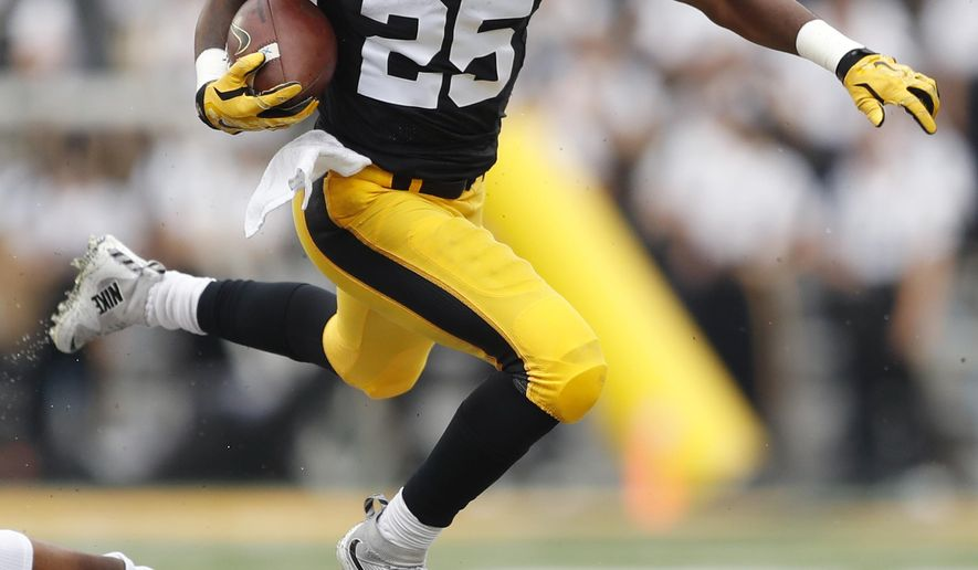 Iowa running back Akrum Wadley (25) leaps over Illinois linebacker Dele Harding during the first half of an NCAA college football game, Saturday, Oct. 7, 2017, in Iowa City, Iowa. (AP Photo/Charlie Neibergall)