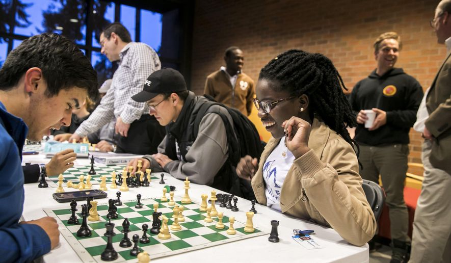 In this Sept. 19, 2017, photo, Phiona Mutesi, center, plays chess with Walter Borbridge, left, during their first chess team meeting in Kirkland, Wash. Mutesi and Benjamin Mukumbya, standing in background, grew up together in Uganda and learned to play competitive chess in a local program that led them to international success. (Bettina Hansen/The Seattle Times via AP)