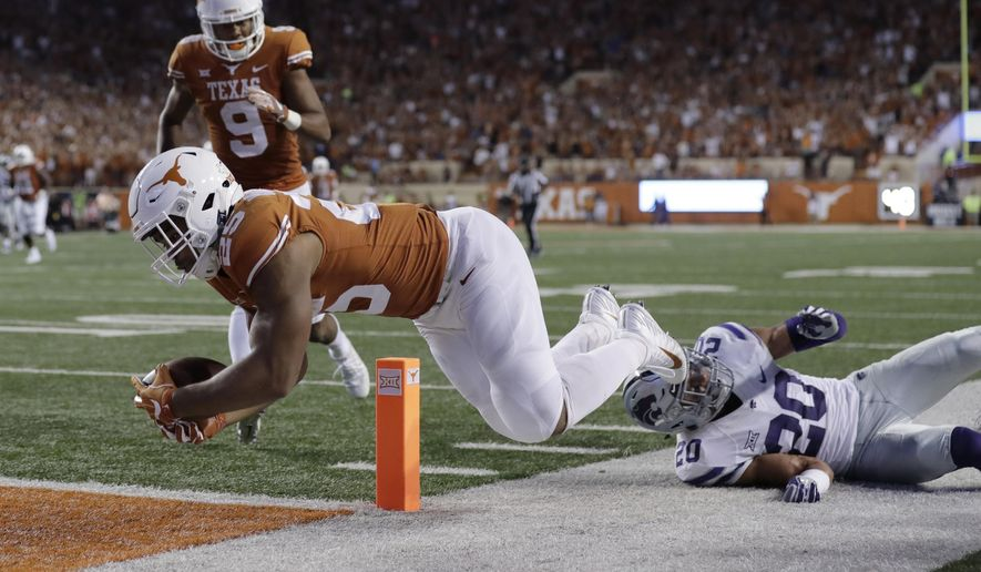 Texas running back Chris Warren III (25) dives past Kansas State defensive back Denzel Goolsby (20) to score a touchdown during the first half of an NCAA college football game, Saturday, Oct. 7, 2017, in Austin, Texas. (AP Photo/Eric Gay)