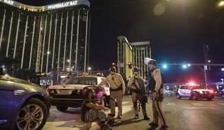 FILE - In this Sunday, Oct. 1, 2017 file photo, police officers stand at the scene of a mass shooting near the Mandalay Bay resort and casino on the Las Vegas Strip, in Las Vegas. Police who have yet to find Stephen Paddock's motive for the massacre said Friday that they will enlist the public's help. Billboards will serve as a stark reminder that investigators remain stumped about what drove a gunman to mow down concertgoers from a perch in the high-rise casino hotel. (AP Photo/John Locher, File)
