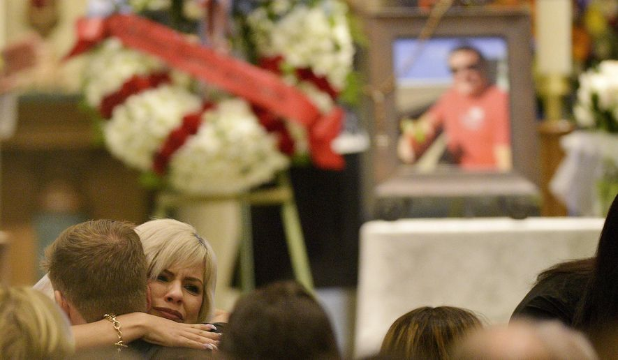 A mourner hugs family members during a memorial service for Jack Beaton at St. Elizabeth Ann Seton Catholic Church in Bakersfield, Calif., on Saturday, Oct. 7, 2017. Beaton was a victim of the Oct. 1 mass shooting in Las Vegas. (AP Photo/Silvia Flores)
