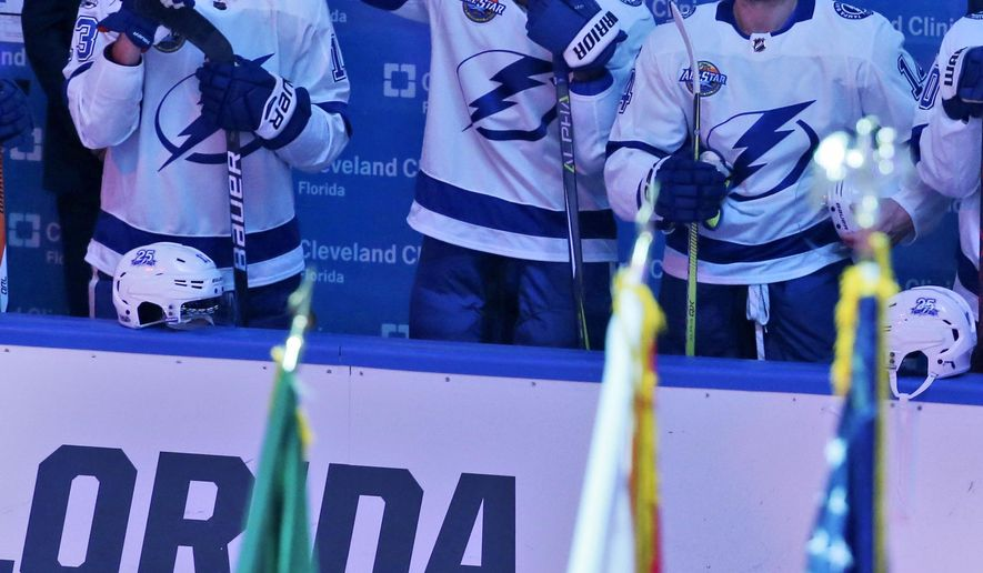 Tampa Bay Lightning right wing J.T. Brown, center, raises his fist in the air during the singing of the national nnthem before the start of an NHL hockey game between the Florida Panthers and the Tampa Bay Lightning, Saturday, Oct. 7, 2017, in Sunrise, Fla. (AP Photo/Wilfredo Lee),