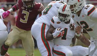 Miami's Mark Walton looks for running room against Florida State's defense in the first quarter of an NCAA college football game, Saturday, Oct. 7, 2017, in Tallahassee, Fla. (AP Photo/Steve Cannon)