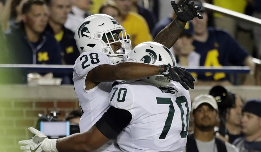 Michigan State running back Madre London (28) celebrates his rushing touchdown with guard Tyler Higby (70) during the first half of an NCAA college football game against Michigan, Saturday, Oct. 7, 2017, in Ann Arbor, Mich. (AP Photo/Carlos Osorio)