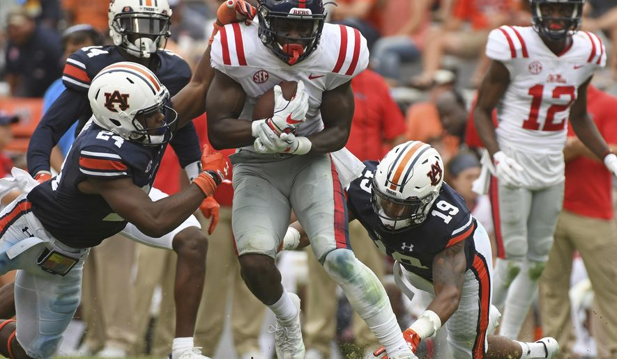 Auburn defensive backs Daniel Thomas (24) and Nick Ruffin (19) attempt to tackle Mississippi wide receiver A.J. Brown (1) during the second half of an NCAA college football game in Auburn, Ala., Saturday, Oct. 7, 2017. Auburn won 44-23. (AP Photo/Thomas Graning)