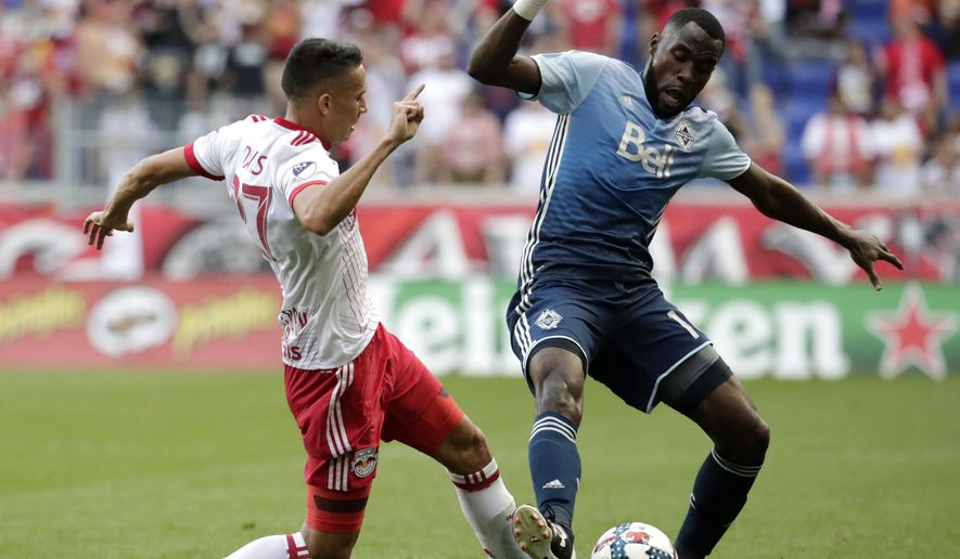 New York Red Bulls midfielder Sean Davis, left, and Vancouver Whitecaps midfielder Tony Tchani compete for the ball during the first half of an MLS soccer match, Saturday, Oct. 7, 2017, in Harrison, N.J. The Red Bulls won 3-0. (AP Photo/Julio Cortez)