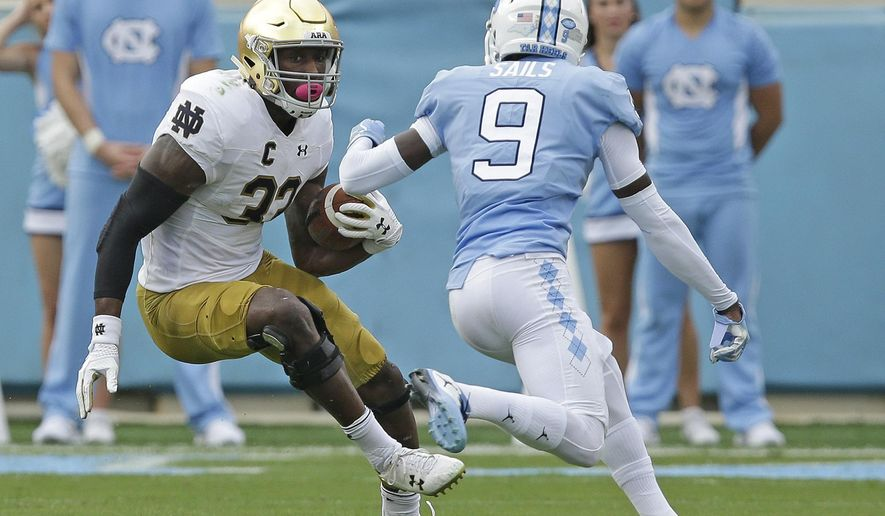 Notre Dame's Josh Adams (33) runs the ball while North Carolina's K.J. Sails (9) moves in for the tackle during the first half of an NCAA college football game in Chapel Hill, N.C., Saturday, Oct. 7, 2017. (AP Photo/Gerry Broome)