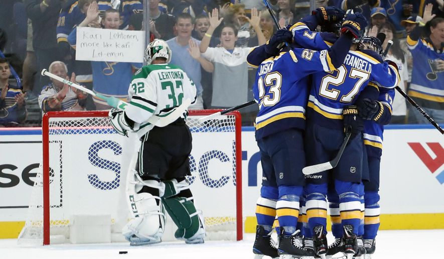 Teammates surround St. Louis Blues' Joel Edmundson after his goal past Dallas Stars goalie Kari Lehtonen, left, of Finland, during the first period of an NHL hockey game Saturday, Oct. 7, 2017, in St. Louis. (AP Photo/Jeff Roberson)